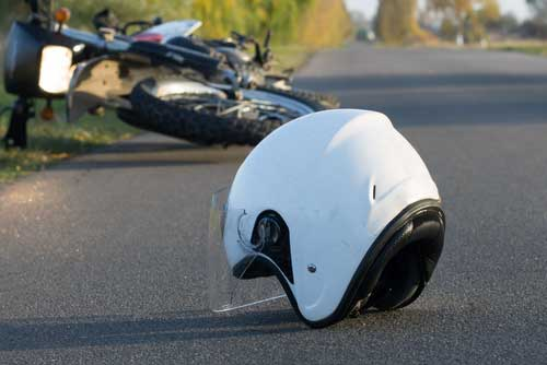 A motorcycle and a helmet lying in the road.
