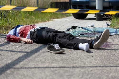 A pedestrian lying in the road after being struck by a car.
