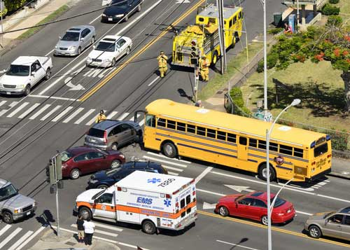 A bus accident at a busy intersection involving multiple cars.