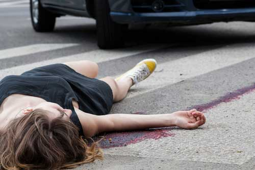 A woman lying in the street after a pedestrian accident.