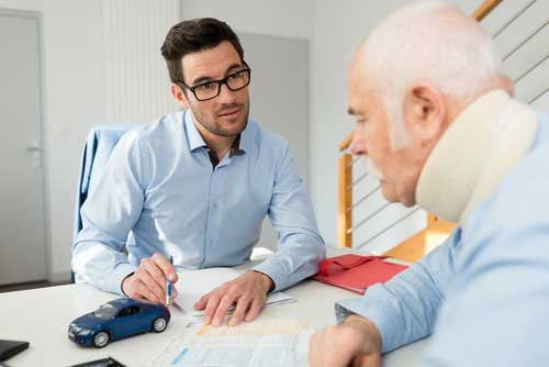 An injured, elderly man sitting with his personal injury attorney.