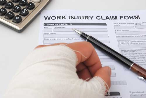 A man with an injured hand signing a workers compensation document.
