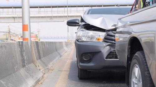 A rear-end accident between two sedans on a highway.