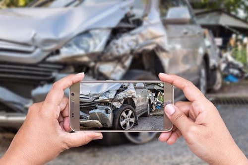 A man taking photographs of his car after an accident to preserve evidence.