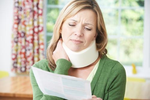A woman with an injured neck from a car accident looking at an insurance settlement offer.