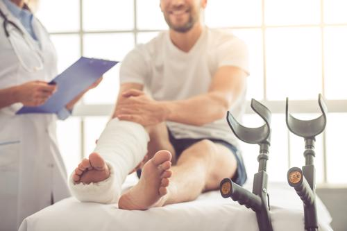 A man with an ankle injury seeking treatment from a doctor.