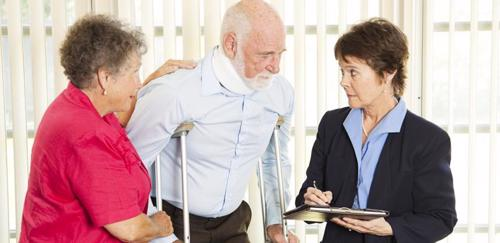 An older man on crutches meeting with a Stonecrest personal injury lawyer.