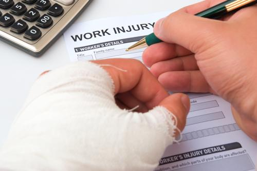 A man with a bandaged hand filling out a workplace injury report form.
