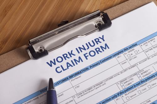 A work injury form and a pen on a clipboard.