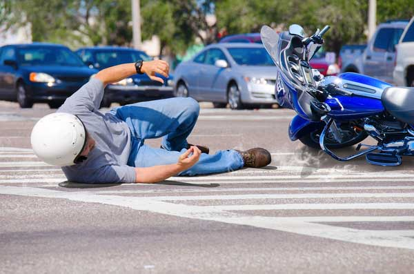 Motorcycle rider falling off bike at intersection